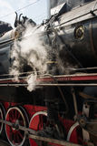 Ancient steam locomotive in steam. Live steam around mechanical Stock Images