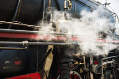 Ancient steam locomotive in steam. Live steam around mechanical Royalty Free Stock Images