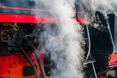 Ancient steam locomotive in steam. Live steam around mechanical Royalty Free Stock Photo