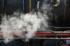 Ancient steam locomotive in steam. Live steam around mechanical Stock Photography