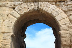 Ancient stone arch. An ancient Roman arch of travertine on a background of a blue sky with clouds Stock Images