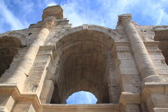 Ancient stone arch. An ancient Roman arch of travertine on a background of a blue sky with clouds stock photos