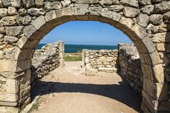 Ancient stone arch against the blue sea. Stock Image