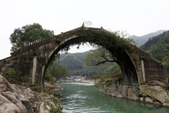 An ancient stone arch bridge in the mountains near Shanghai. A woman holding a gauze on it, the green stream flowing below Stock Images