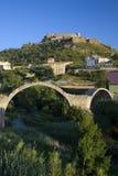 Ancient stone arch bridges with a background of Parador de Cardona, a 9th Century medieval hillside Castle, near Barcelona, Catalo Stock Photo