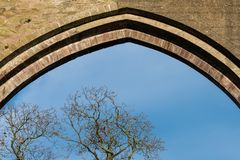 Ancient stone arch in the medieval ruins of an old Irish church frames a blue sky and trees with bare branches royalty free stock photos