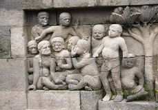 Ancient stone bas-relief, Buddist temple Borobudur, Yogyakarta. Ancient stone bas-relief with group of people - mens and womens, Buddist temple Borobudur Stock Photo