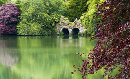 Ancient stone bridge by a lake. Peaceful English scene with calm lake, bridge, and trees Royalty Free Stock Images