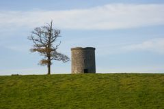 An ancient round tower with an old dying ash tree beside it in a farmers field at Crawfordsburn in Northern Ireland. An ancient stone built round tower with an royalty free stock photos