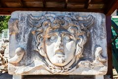 Ancient stone carving of Medusa Head. Stock Photo