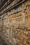Ancient stone carvings in the Buddhist temple. Ancient stone carvings in the Borobudur Buddhist temple on Java, Indonesia Royalty Free Stock Image