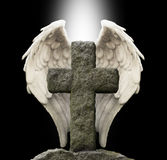 Ancient Stone Cross and Guardian Angel Wings. Old masonry graveyard cross with a pair of white angel wings behind on a black background with a shaft of central Stock Images