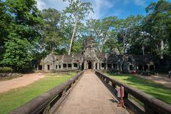 Ancient stone door with clear blue sky, Ta Prohm temple ruins, A. View of an ancient stone door with clear blue sky, Ta Prohm temple ruins, Angkor, Cambodia royalty free stock photography