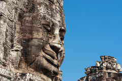 Ancient stone smiling face of the Prasat Bayon Wat temple in the jungle, Angkor wat, Cambodia. Angkor Wat isthe largest Royalty Free Stock Photo