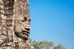 Ancient stone smiling face of the Prasat Bayon Wat temple in the jungle, Angkor wat, Cambodia. Angkor Wat isthe largest Royalty Free Stock Photos