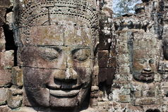 Ancient stone faces. Ancient faces carved into an old ruined stone wall Royalty Free Stock Photo