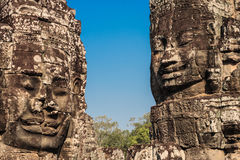 Ancient stone smiling faces of the Prasat Bayon Wat temple in the jungle, Angkor wat, Cambodia. Angkor Wat isthe largest Stock Images
