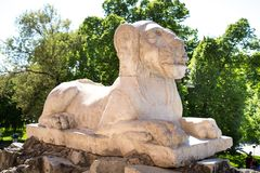 Ancient stone figure of a lying lion. On the background of green trees and blue sky stock photos