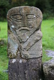 Ancient stone figure. An ancient stone figure stands in a cemetery royalty free stock image