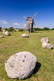 Ancient stone henge in front of traditional windmill Royalty Free Stock Photography