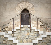 Ancient stone made wall with a rusty metallic door and a staircase Stock Photos