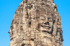Ancient stone smiling face of the Bayon Wat temple in the jungle, Angkor wat, Cambodia. Angkor Wat isthe largest Stock Photos