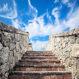Ancient stone stairway under cloudy sky. Ancient stone stairway goes up under blue cloudy sky background Stock Images