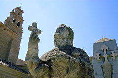 Ancient stone statue and aisled church, Spain Royalty Free Stock Image