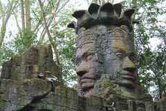 An ancient stone statue of twin faces in a temple  Stock Image