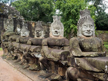 Ancient stone statutes in Cambodia. Statutes of stone asura or demons with newly moulded heads at Angkor Thom, ancient capital of Khmer empire Stock Image