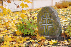 Ancient stone unknown tombstone with a relief cross. Royalty Free Stock Image