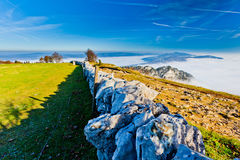 Ancient Stone Wall. Stone Wall at Creux du Van, Switzerland with early morning fog at the valley below the mountains Royalty Free Stock Photography