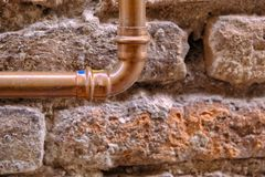 Ancient stone wall and copper pipe. Large size close up photo of an old brick wall and old copper water pipe. You may see almost colorless light beige stone wall royalty free stock photos