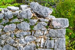 An ancient stone wall of a ruined house amongst the grass. Old house, ruins, background.  Royalty Free Stock Image