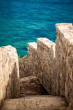 Ancient stone wall with stairs leading to blue sea Royalty Free Stock Photography