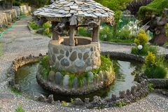 Ancient stone well for water. In the garden stock images