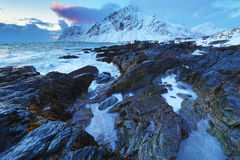 Ancient stones on the shores of cold Norwegian Sea at evening time. Lofoten islands. Beautiful Norway landscape. Stock Photography