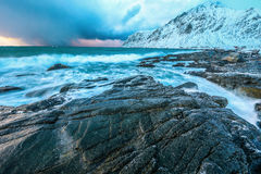 Ancient stones on the shores of cold Norwegian Sea at evening time. Lofoten islands. Beautiful Norway landscape. Stock Photos