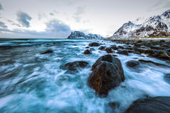 Ancient stones on the shores of cold Norwegian Sea at evening time. Lofoten islands. Beautiful Norway landscape. Royalty Free Stock Photo