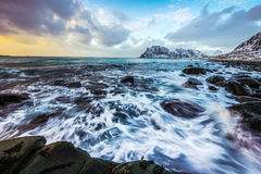 Ancient stones on the shores of cold Norwegian Sea at evening time. Lofoten islands. Beautiful Norway landscape. Royalty Free Stock Images
