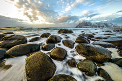 Ancient stones on the shores of cold Norwegian Sea at evening time. Lofoten islands. Beautiful Norway landscape. Stock Image