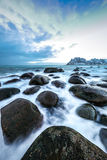 Ancient stones on the shores of cold Norwegian Sea at evening time. Lofoten islands. Beautiful Norway landscape. Royalty Free Stock Image