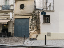 Ancient stonework juts out between modern walls on rue de Cluny, Stock Image