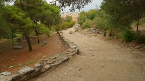 Ancient stony road through park to modern city, decaying old infrastructure