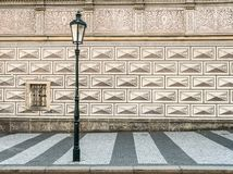 Ancient street lamp in front of a wonderful patterned house wall in Prague - Czech Republic. Ancient street lantern in front of a wonderful patterned house wall royalty free stock photography
