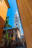 Ancient Street in Modena with a view of the white tower on blue sky background. Ancient Street in Modena, Italy with houses with yellow walls overlooking the Royalty Free Stock Photos