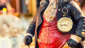 Ancient style clock on the statuette of man Royalty Free Stock Photo