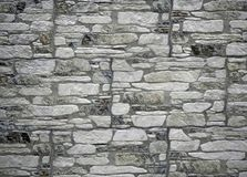 Ancient style wall cladding for interiors made of artificial stone panels. The stoneware shapes are white and black, irregular and of different sizes royalty free stock photography