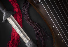 Ancient sword and guqin. Ancient tai chi sword for forms of Xin Yi Hunyuan Taijiquan and ancient stringed instrument GuQin Royalty Free Stock Photo