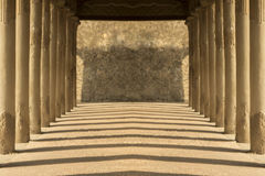 Ancient symmetrical hallway with evening shadows and brick work Royalty Free Stock Photo